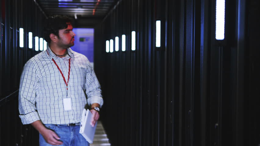 People working in computer server room data center. Walking along rows of super computers, racks and airconditioned IT cpu's.