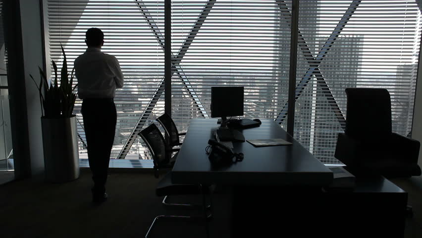 Businessman looking over city view from executive office. High quality HD video footage