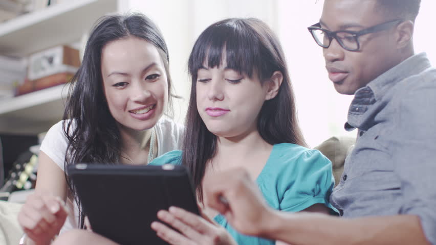 Young people with technology. Student house accommodation. Flat share with teenagers or young adults using digital tablets, laptops and cell phones.