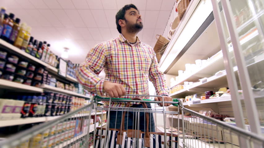 Customers shopping in a Supermarket and browsing products. Shopping trolley being filled with groceries and food. | Shutterstock HD Video #4501508