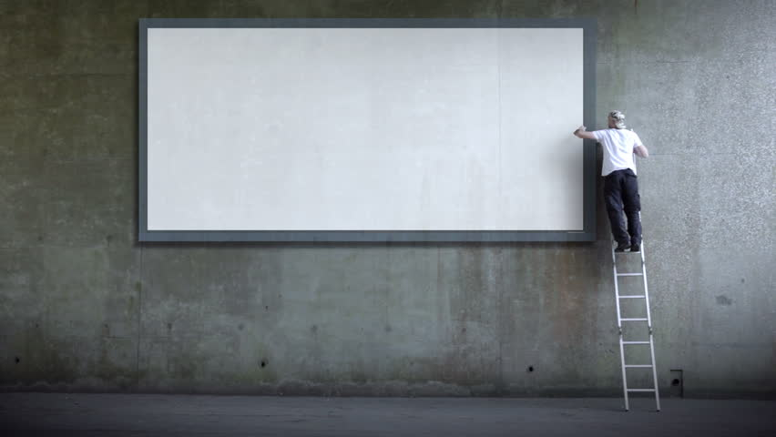 Man erects billboard poster for advertising. Blank wall for copy space advertising. Part of a series of artistic clips I'm calling 'Wall Street'.
