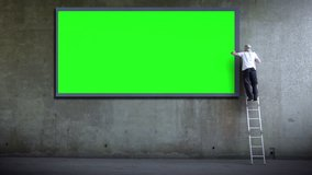 Billboard poster advertising. Green screen wall for copy space advertising. Man erects billboard. Part of a series of artistic clips I'm calling 'Wall Street'.