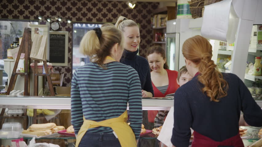 Happy customers being served by friendly staff at the bakery counter of a local cafe or grocery store.