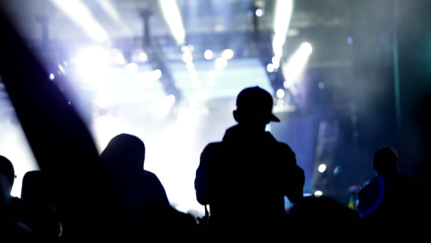Fan at a life concert making a video or photo with his cell phone, some visible noise due high ISO, soft focus | Shutterstock HD Video #4519223