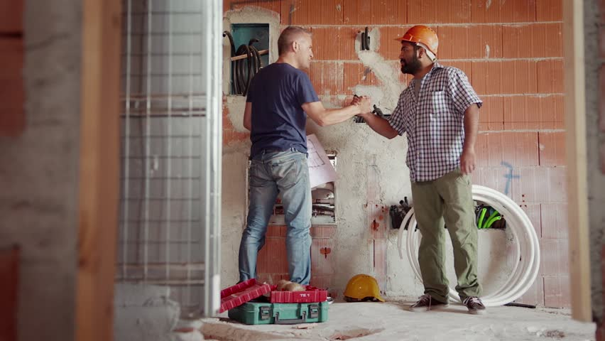 People and teamwork, team of two men at work in construction site, manual workers saluting and collaborating. Part 4 of 11 | Shutterstock HD Video #4522199
