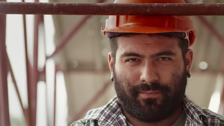 Young hispanic man at work in construction site, portrait of serious manual worker with helmet looking at camera. Part 2 of 11