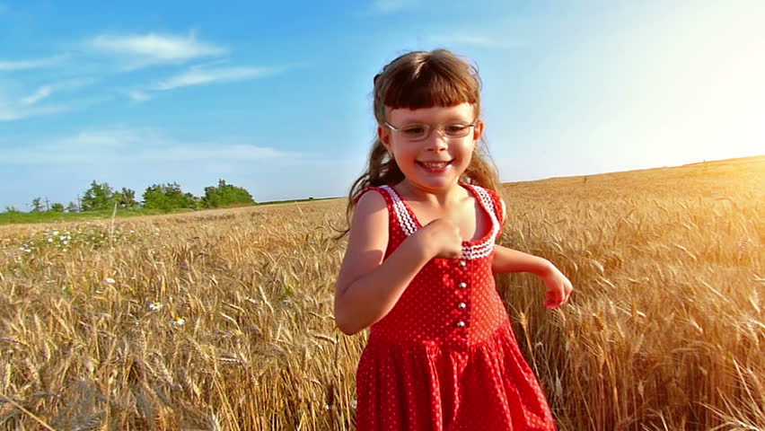 Little girl running cross the wheat field at sunset. Slow motion, high speed camera.