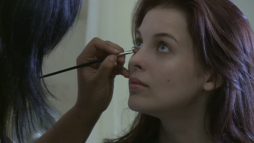 Young actress being made up before a filming session.