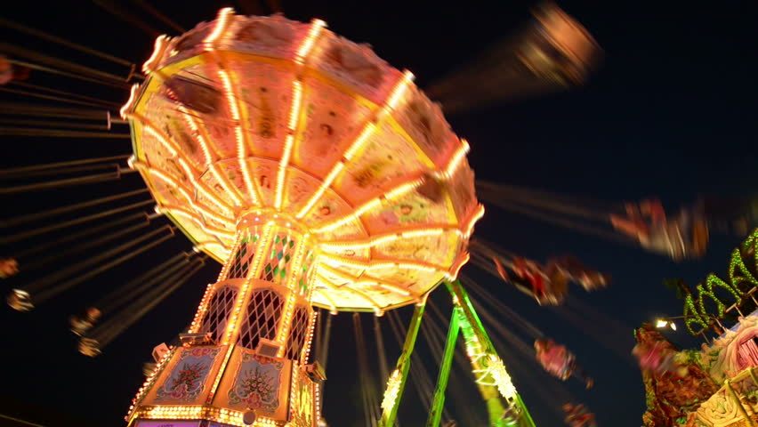 A classic carousel on a funfair like Oktoberfest. All recognizable people or names/logos are blurred out by motion or hand. 11055   Royalty-Free Stock Footage #4532777