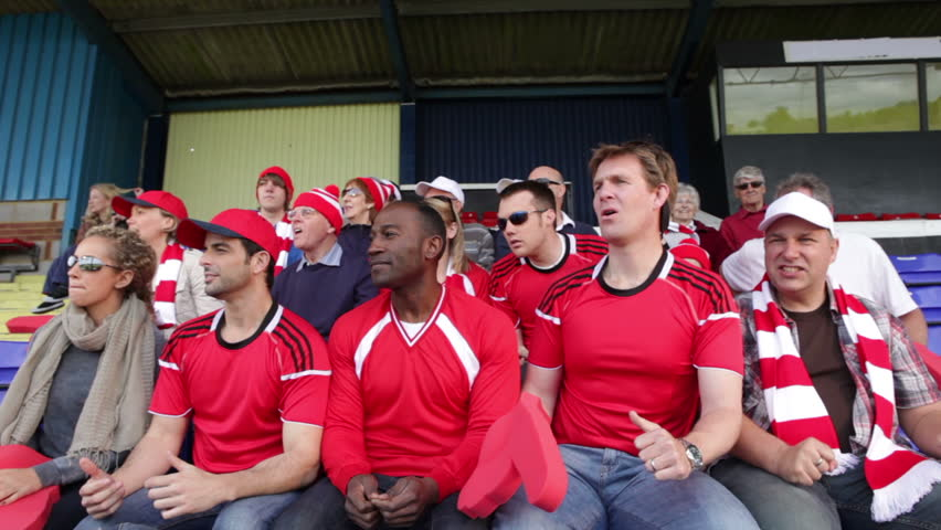 Enthusiastic crowd of spectators watching a sports game or football match and reacting