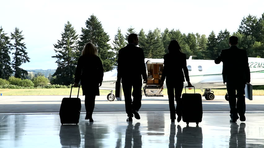 Businesspeople walk out to jet