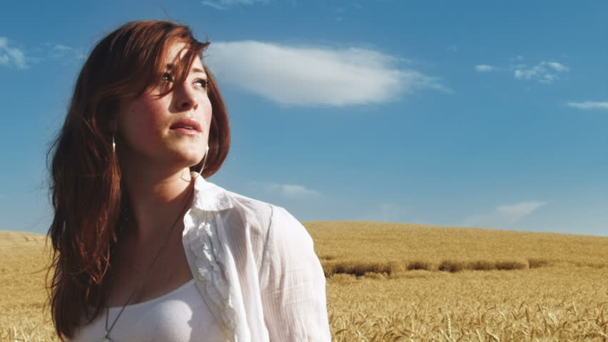 Young woman out in a wheat field gazes off into the distance and then turns and stares at the camera   Shutterstock HD Video #4562630
