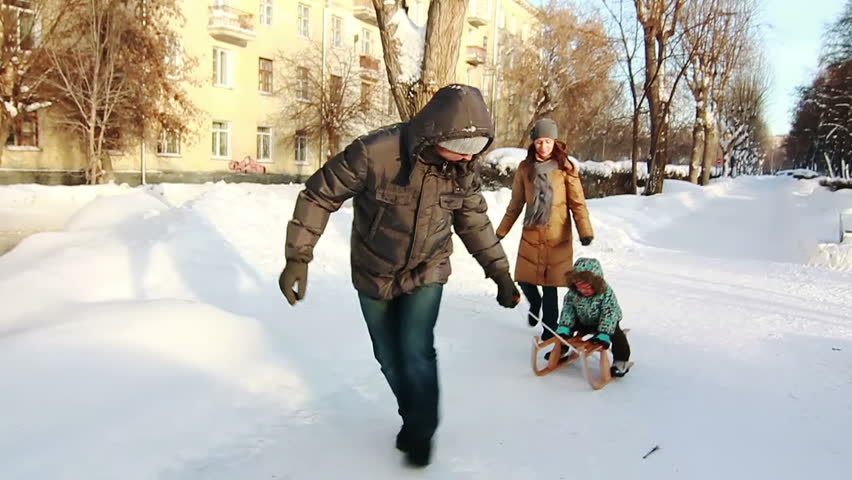 Slow motion shot of father, who is pulling his son in sled. Park in winter.