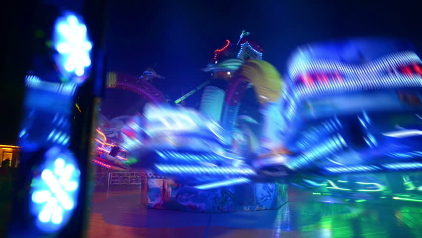 A twisting carousel on a funfair like Oktoberfest. All recognizable people or names/logos are blurred out by motion or hand. 11066   Royalty-Free Stock Footage #4571234