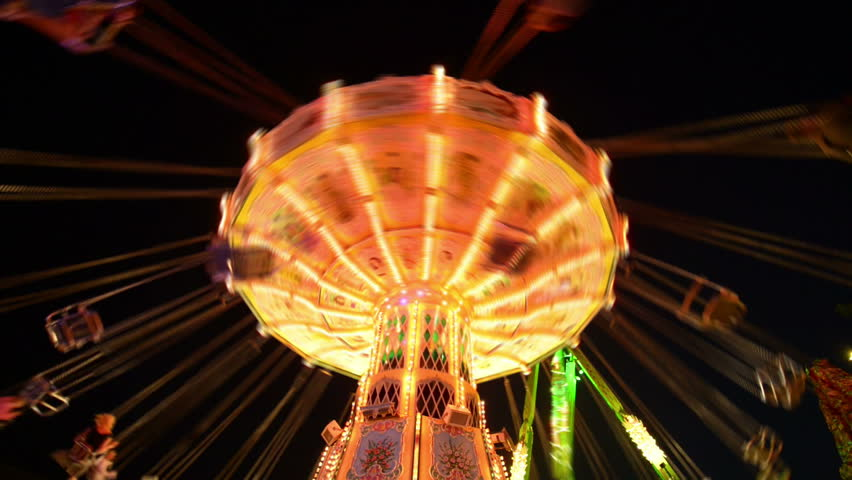 Time lapse of a classic carousel on a funfair like Oktoberfest. All recognizable people or names/logos are blurred out by motion or hand. 11065   Royalty-Free Stock Footage #4571237