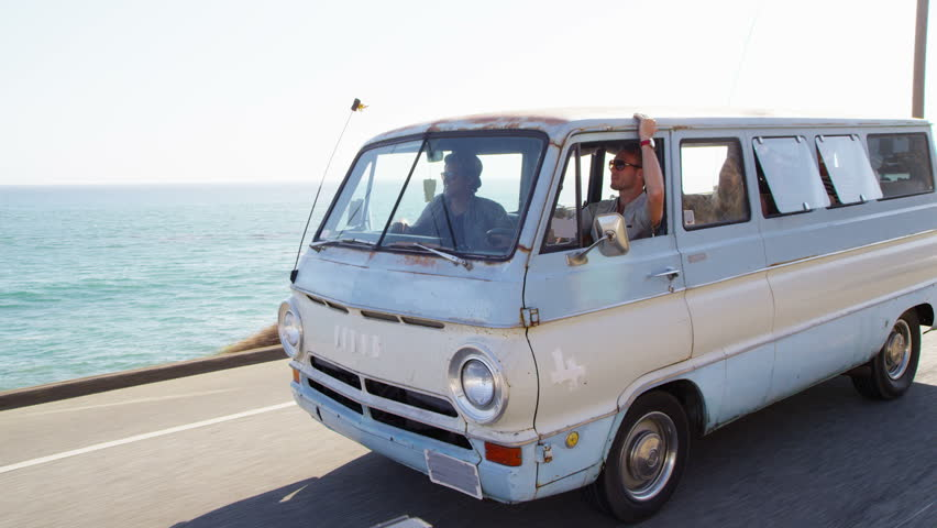Group of young people on road trip driving van