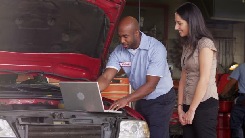 Auto repairman shows customer laptop computer