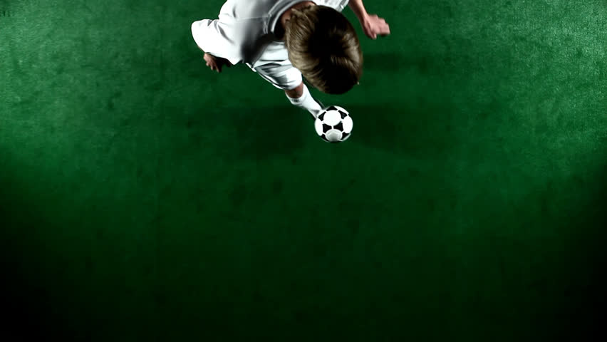 A soccer, or football, player that is dramatically and artistically lit, on an artificial field pitch on a black background, juggles the ball. As seen from above looking down. #4604918