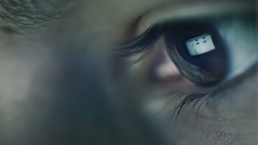 Closeup shot of boy eye surfing internet at night