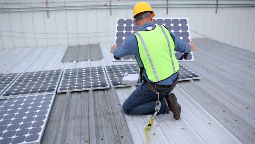 Contractor installing solar panels on rooftop