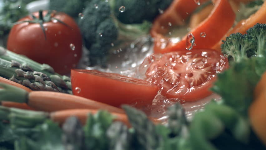 Tomato splashing into water, slow motion