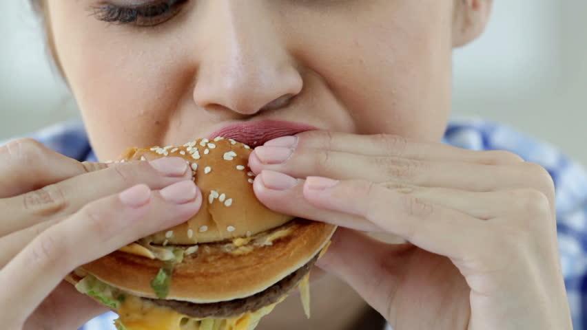 Close-up of a girl enjoying a fresh hamburger
