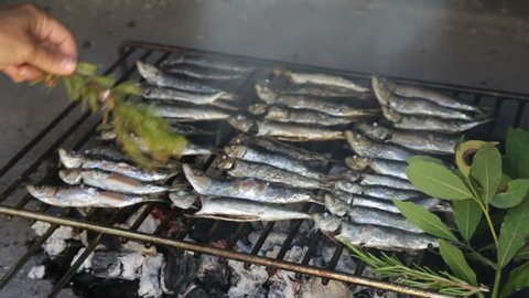 Fresh Mediterranean fishes on traditional BBQ fireplace, oiling with virgin olive oil, selective focus