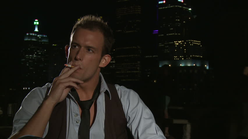Young man enjoying a cigarette with the city of Toronto lit up behind him. | Shutterstock HD Video #4627067