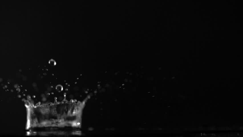 Water drop making splash on black background shooting with high speed camera, phantom flex.