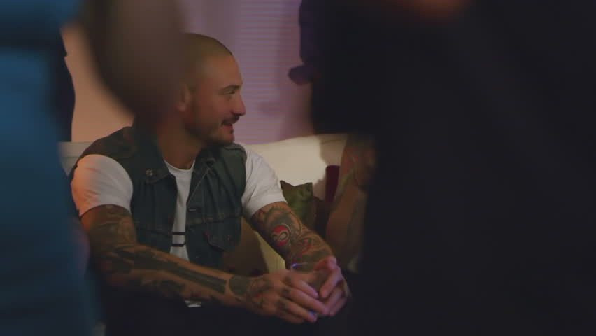 During a party, a young woman sits with a guy and looks at his tattoos. Medium shot. | Shutterstock HD Video #4636958