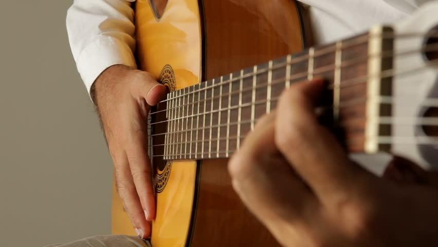 Hands playing flamenco with a spanish guitar seen from the guitar headstock