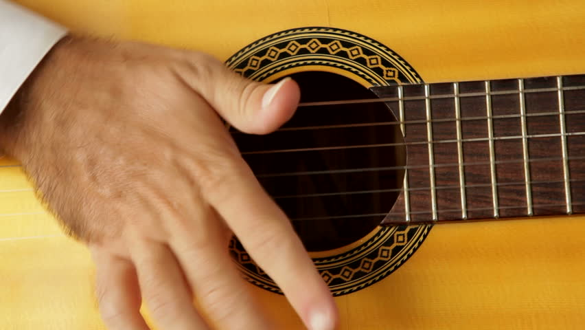Camera pan on a man playing flamenco with a spanish guitar with  strings muted