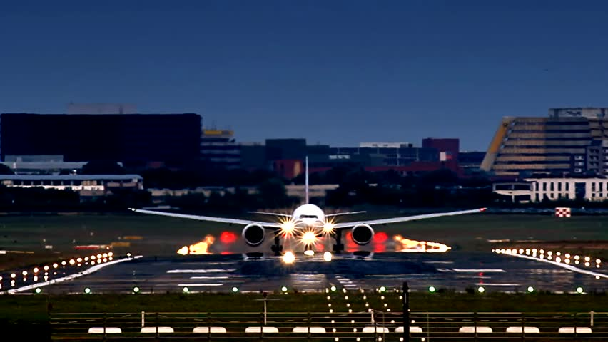 Giant Airliner Boeing 777 during take off from Hamburg airport (HAM). Late evening, blue sky and runway ilumination. Visible heat haze, cause of high temperature on the runway.