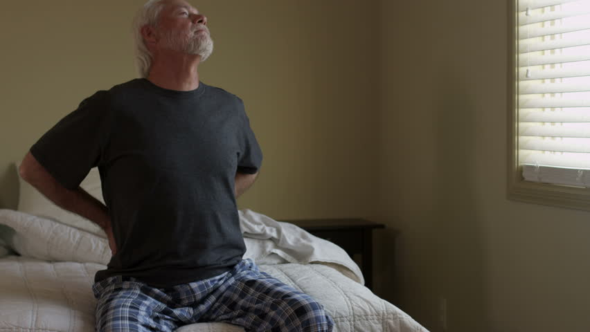 Elderly man with pain sitting on bed