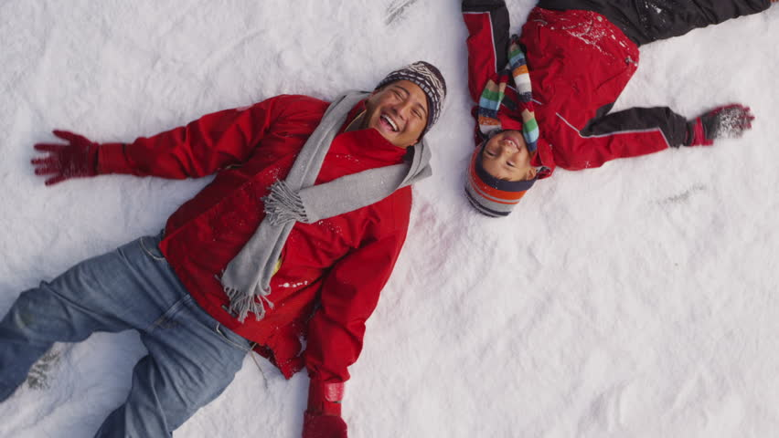 Father and son making snow angels