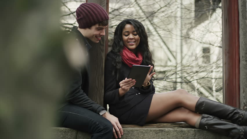 A cute young couple sit together and look through their digital tablet. Medium shot. | Shutterstock HD Video #4663733