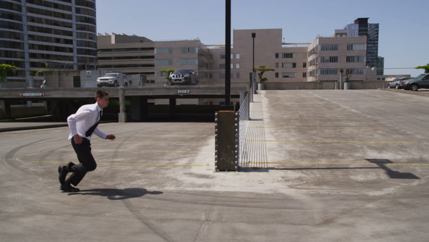 Businessman jumps over car in parking lot, slow motion