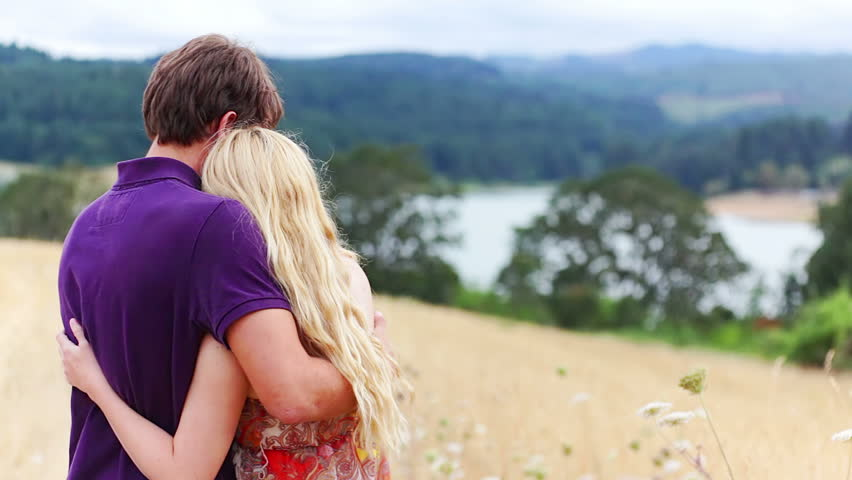 Young attractive couple hug each other in a field over looking a lake. Medium shot. | Shutterstock HD Video #4666541