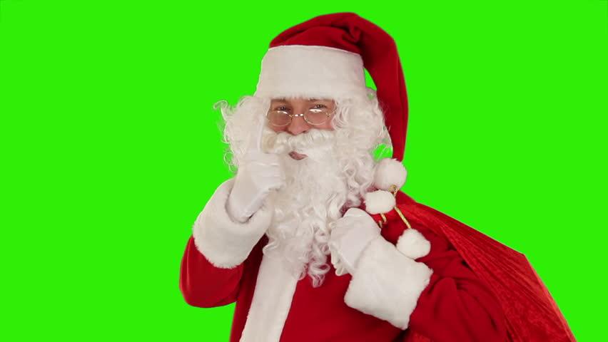 Santa Claus carrying his bag, looks at the camera sends a kiss and wave, Green