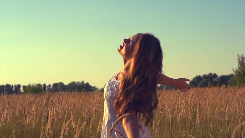 Beauty Girl with Healthy Long Hair Outdoors. Happy Smiling Young Woman Enjoying Nature. Beautiful Young Woman having Fun in the Meadow. Freedom concept. Sunset