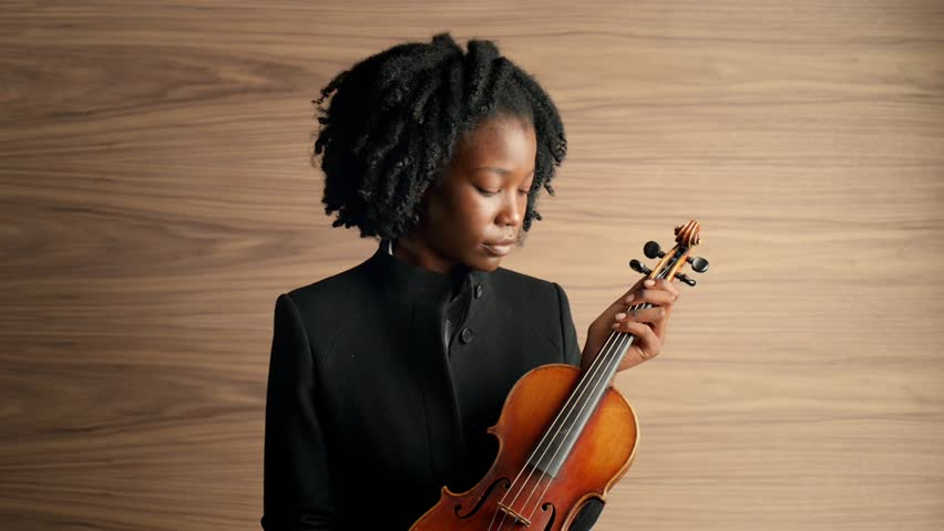 Portrait of classical musician holding violin African American woman
