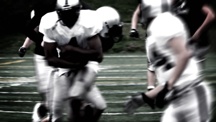 A Running Back receives a handoff and spins to avoid a defender. High contrast, with flashes and time remap.