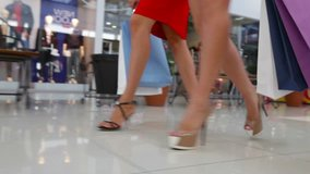 Close-up of shopping girls marching in the mall