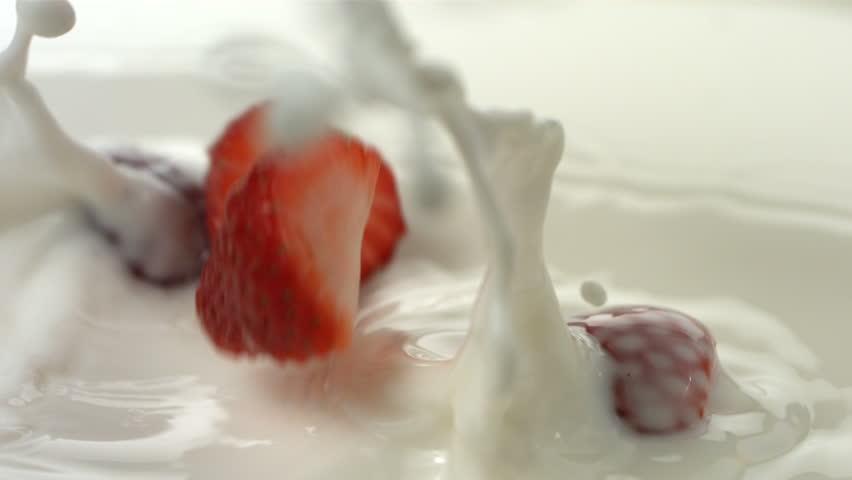 Fresh strawberries splashing into cream, slow motion #4693787