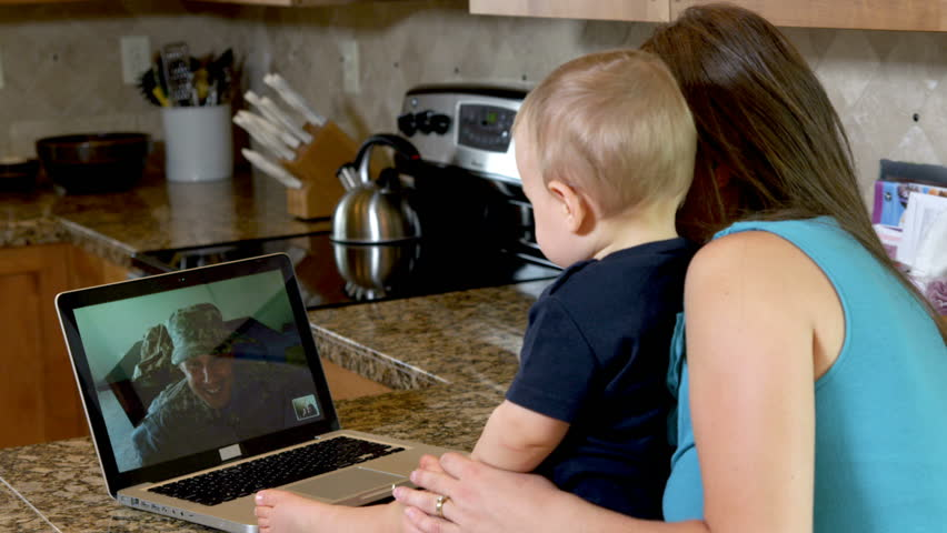 Mother and baby video chat with military father