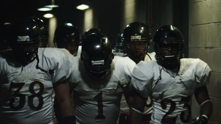 Football team walks down a dark tunnel towards the field before a game