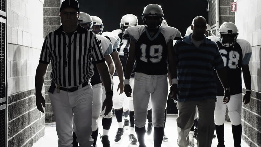 A football team walks down a dark hallway before a game, dramatically lit from behind in slow motion