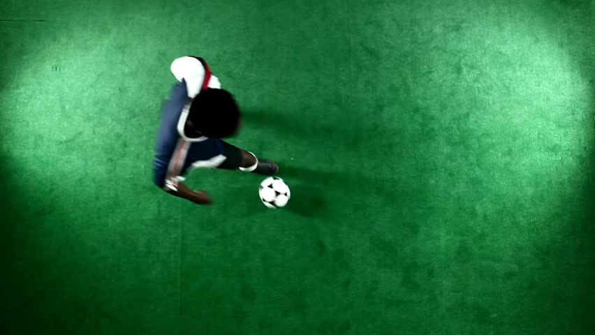 Bird's eye view of a soccer player on a green background juggling the ball after receiving it off his chest #4710566