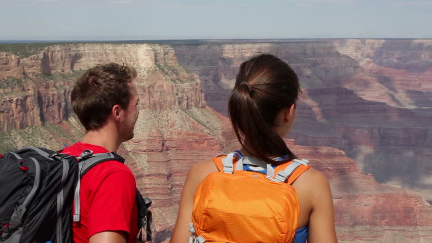 Hikers - people hiking Grand Canyon. Young happy couple enjoying hike and active outdoor lifestyle. Happy young couple, multicultural Asian woman and Caucasian man outside, Arizona, United States.