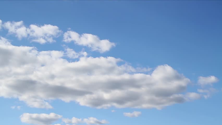 Beautiful white clouds soar across the screen in time lapse fashion over a deep blue background. 30 second loop.